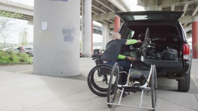 vídeos de stock e filmes b-roll de adaptive athlete unloading a bicycle - paralisia