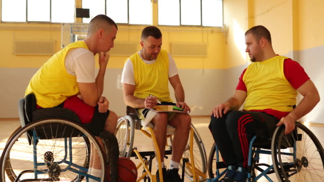 adaptive athletes in wheelchairs talking about basketball strategy - wheelchair basketball stock videos & royalty-free footage