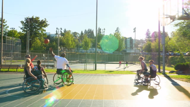 ms adaptive athletes playing basketball game on outdoor court on summer afternoon - wheelchair basketball stock videos and b-roll footage