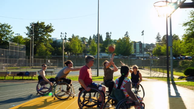 pan adaptive athletes playing basketball game on outdoor court on summer afternoon - disability stock-videos und b-roll-filmmaterial