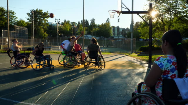 ms adaptive athletes playing basketball game on outdoor court on summer evening - drive ball sports stock videos & royalty-free footage
