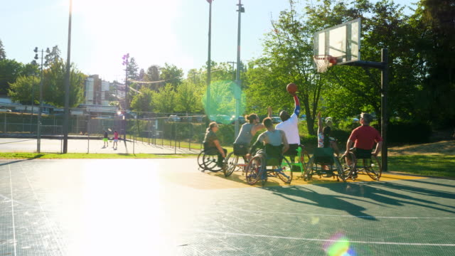 ms adaptive athletes playing wheelchair basketball game on summer evening - wheelchair basketball stock videos and b-roll footage