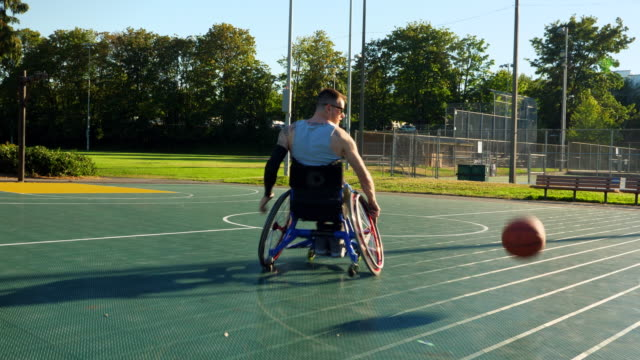 ts adaptive athletes playing wheelchair basketball game on summer evening - 車いす点の映像素材/bロール