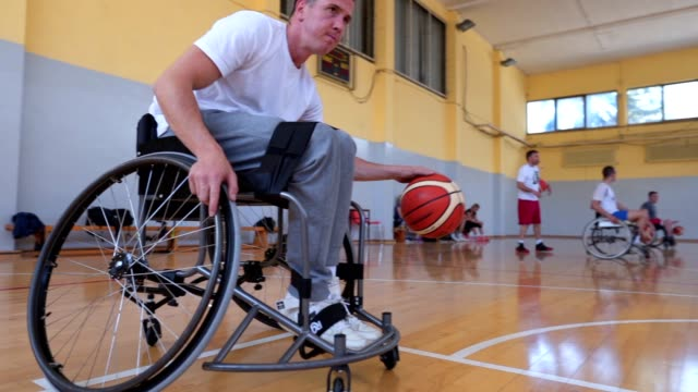 adaptive basketball athlete exercising dribbling on a sports court with his team - wheelchair basketball stock videos & royalty-free footage