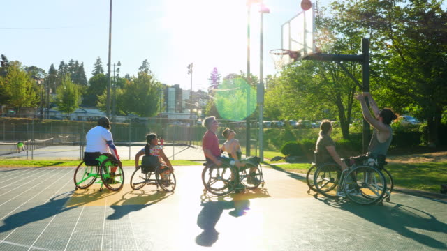 ms adaptive basketball athletes practicing on outdoor court on summer evening - wheelchair basketball stock videos and b-roll footage