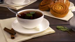 add a piece of sugar to the tea with mint. the concept of a morning breakfast