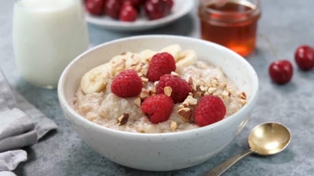 vidéos et rushes de add nuts to oatmeal porridge bowl - bol et saladier