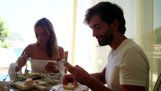 addicted to smart phone. couple having breakfast and using phones - distracted stock videos & royalty-free footage