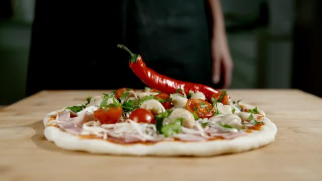 vidéos et rushes de slo mo ajouter un piment sur la pizza - piment