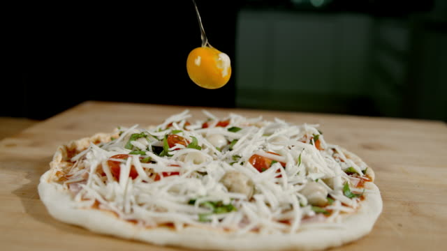 slo mo adding a raw egg on the pizza - recipe stock videos & royalty-free footage
