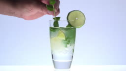 adding a sprig of mint in a mojito