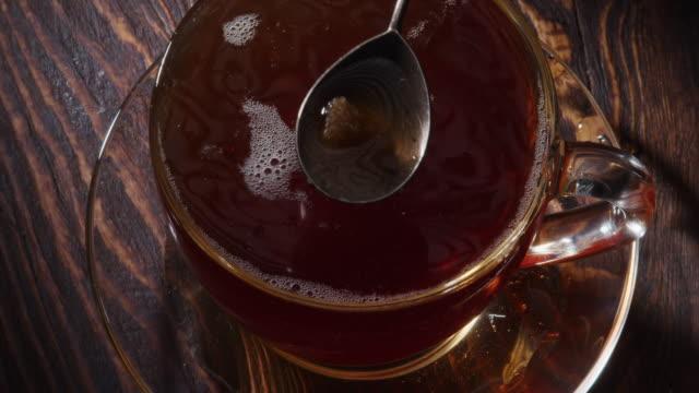 vídeos de stock e filmes b-roll de adding a sugar cube into the cup of tea - chávena