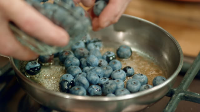 adding blueberries into a pan with melted butter and brown sugar - fruit stock videos & royalty-free footage