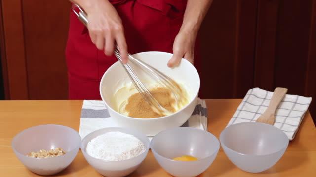 adding brown sugar to mixture for baking - schüssel stock-videos und b-roll-filmmaterial