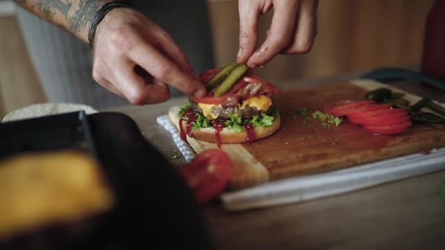 stockvideo's en b-roll-footage met laatste details toe te voegen aan heerlijke cheeseburgers - burger menselijke rol