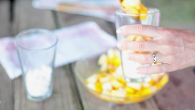 vidéos et rushes de adding fruit salad to glasses partially filled with crushed meringue - table de pique nique