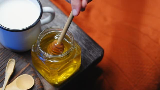 vídeos y material grabado en eventos de stock de agregar miel a la leche - taza sin platillo