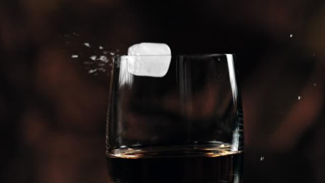 slo mo eiswürfel zu einem whiskey hinzufügen - eiswürfel stock-videos und b-roll-filmmaterial