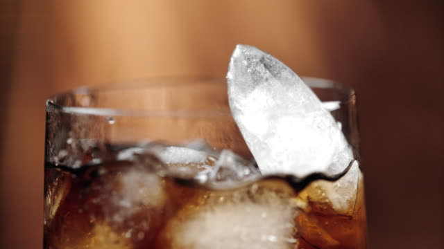 slo mo aggiunta di ghiaccio a una bevanda alla cola - cubetto di ghiaccio video stock e b–roll