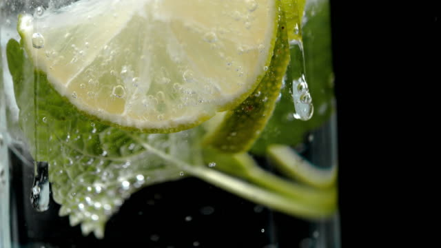 slo mo adding ice to a lime drink - carbonated stock videos & royalty-free footage
