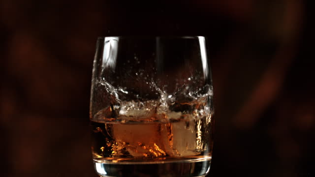 slo mo adding ice to a whiskey - ice stock videos & royalty-free footage