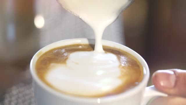 adding milk cream on coffee latte with spoon - saucer stock videos & royalty-free footage