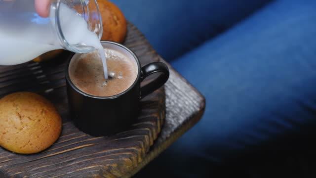 hinzufügen von milch in kaffeetasse - ecke eines objekts stock-videos und b-roll-filmmaterial