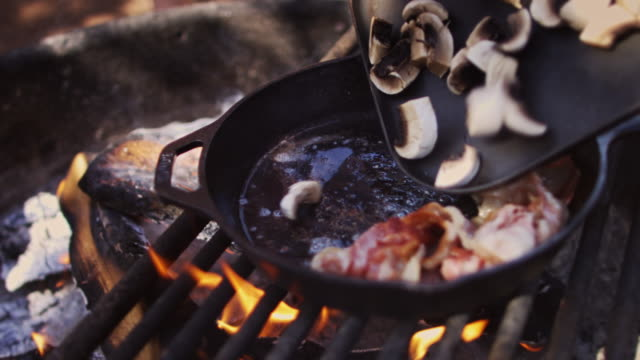 Adding Mushrooms to Pan Over Campfire