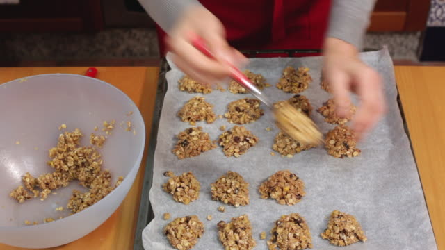 adding oatmeal cookie dough to baking sheet - cookie stock videos and b-roll footage