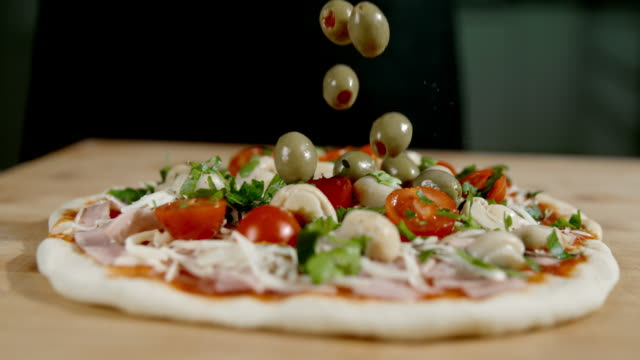 slo mo adding olives on the top of the pizza - super slow motion stock videos & royalty-free footage