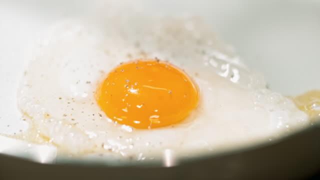 vidéos et rushes de slo mo ajouter poivre à un oeuf que l'on fait frire dans une poêle blanche - yellow