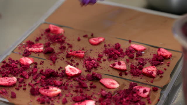 adding raspberry icing onto chocolate bars with strawberry - food processing plant stock videos & royalty-free footage