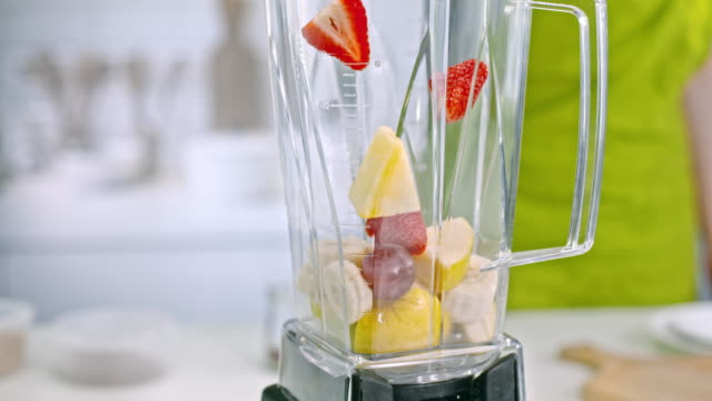 slo mo ld adding strawberries and pineapple into blender jar - chopped food stock videos and b-roll footage