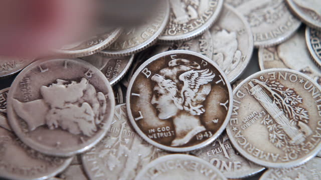 adding to the pile of silver coins - silver metal stock videos and b-roll footage