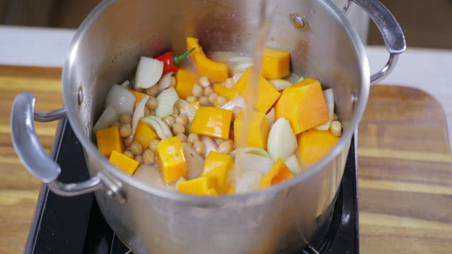 adding water into cooking pot - vegetable stock videos & royalty-free footage