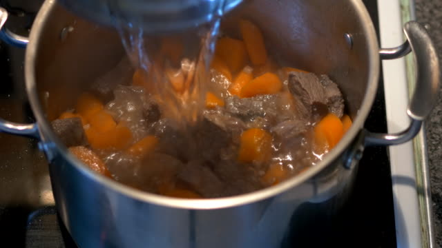 addomg water into beef stew - beef stock videos & royalty-free footage