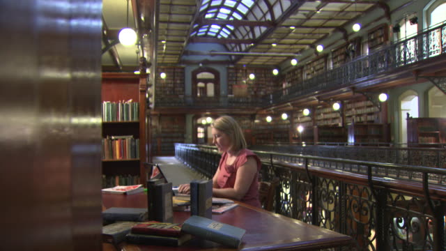 adelaide state library old leather bound books sitting on a shelf woman studying at a desk beautiful victorian wrought iron balustrades and book... - old book stock videos and b-roll footage