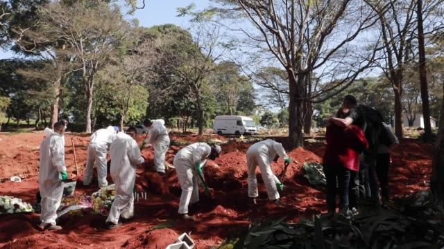 adenilson souza costa, 47 years, and his coworkers wearing protective gear bury a coffin during a burial at vila formosa cemetery amidst the... - brazil stock videos & royalty-free footage