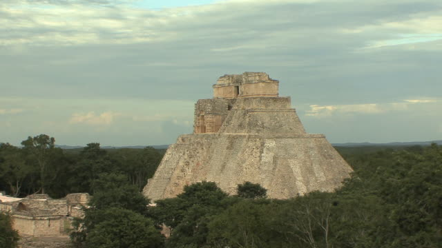WS Adivino (Pyramid of Magician) surrounded with trees at pre-Columbian ruined city of Maya civilization / Uxmal, Yucatan, Mexico