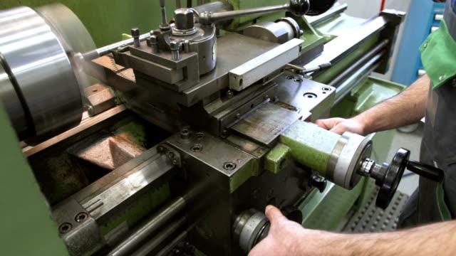 vídeos de stock e filmes b-roll de cu ajustar um torno mecânico para trabalhar metais - operário de linha de produção
