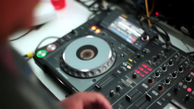 stockvideo's en b-roll-footage met dj adjusts volume on turntable console - hiphop