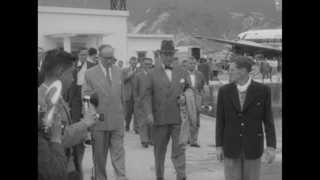 vidéos et rushes de adlai stevenson ii walking away from terminal at hong kong airport with british official and group of officials behind them / stevenson walking away... - adlai stevenson