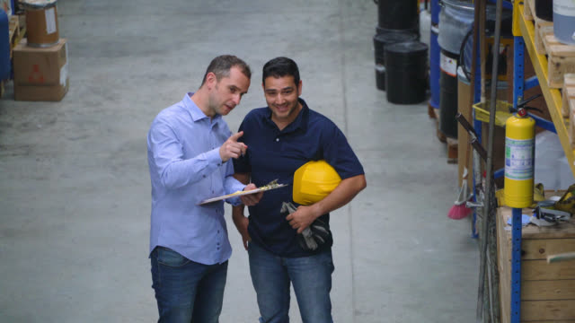 Administrator of a warehouse giving instructions to an employee of the orders to dispatch
