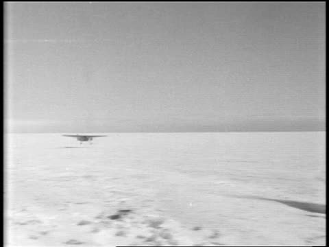 admiral byrd's airplane landing on snowy plain / men in foreground cheer + wave / antarctica - 1920 1929 stock videos & royalty-free footage