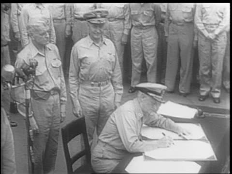 admiral chester nimitz prepares his pen to sign on behalf of the united states / admiral william halsey whispers in general douglas macarthur's ear /... - japanese surrender stock videos & royalty-free footage
