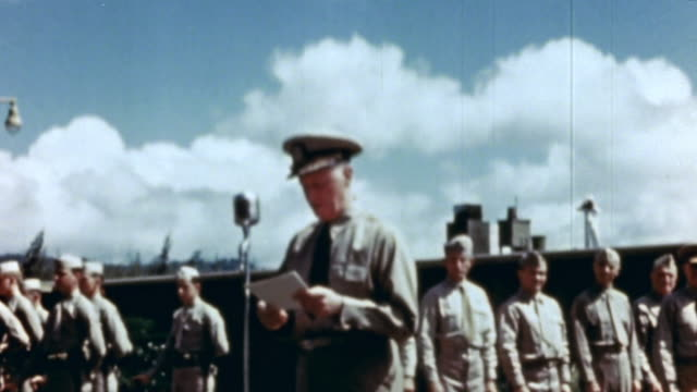 Admiral Chester Nimitz speaking at microphone during medal presentation ceremony
