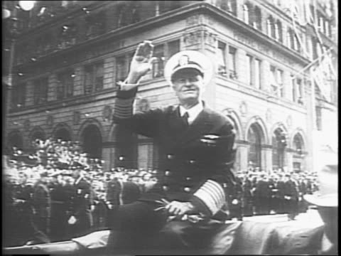 admiral chester nimitz waving to civilians watching the parade / side view of nimitz's parade vehicle and police escorts / camerman filming the... - 映像撮影点の映像素材/bロール
