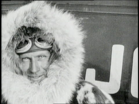 admiral richard e byrd and pilot floyd bennett climb into a fokker f-vii plane before attempting to fly over the north pole in 1926. - 1926年点の映像素材/bロール