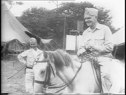 Admiral William 'Bull' Halsey Jr poses in front of press shakes hands with man in front of white horse Halsey on horseback