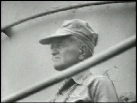 Admiral William 'Bull' Halsey on deck of WS Corsair fighter w/ wings folded rising up from hangar below deck VS Talking off from carrier deck WS In...